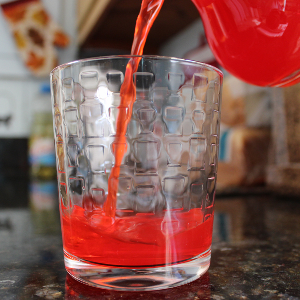 red drink being poured into glass